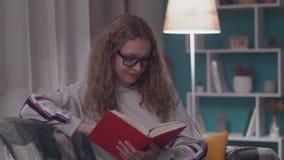 A mulher bonita nova l? um livro de papel em sua sala de visitas acolhedor na noite video estoque