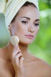 A mulher bonita nova limpa a face com uma escova macia imagens de stock