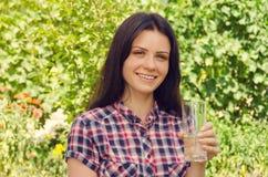 A mulher bonita nova na camisa ocasional guarda um vidro da água e foto de stock royalty free