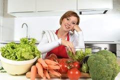 Mulher bonita nova na cozinha vermelha do avental em casa que prepara o sorriso vegetal da bacia de salada feliz Imagens de Stock