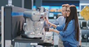 A mulher bonita nova na loja de dispositivos está escolhendo para sua cozinha um misturador que olha e que realiza em suas mãos video estoque