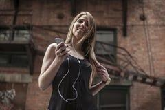 Mulher bonita nova na música de escuta da cidade Imagem de Stock