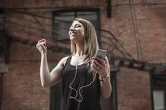 Mulher bonita nova na música de escuta da cidade Fotografia de Stock