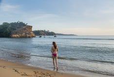 Mulher bonita nova na posição do terno de natação na praia fotografia de stock royalty free