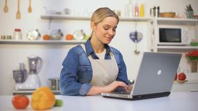 Mulher bonita nova no avental que procura instruções da receita do alimento no blogue do Internet filme