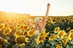 Mulher bonita nova no campo de florescência do girassol Fotos de Stock Royalty Free
