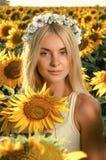 Mulher bonita nova no campo de florescência do girassol Fotografia de Stock Royalty Free