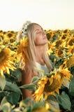Mulher bonita nova no campo de florescência do girassol Imagens de Stock Royalty Free