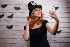Mulher bonita nova no chapéu de Dia das Bruxas que toma um selfie Hallowe fotografia de stock