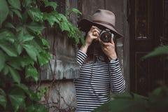 A mulher bonita nova no chapéu está tomando a imagem com câmera antiquado, fora imagens de stock