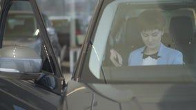 Mulher bonita nova no cinto de segurança azul do desgaste do terno do vestuário formal que senta-se dentro do carro na exposição  filme