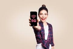 Mulher bonita nova no estilo ocasional que guarda o telefone que olha a câmera e que mostra o Internet 5G na exposição do telefon Fotos de Stock