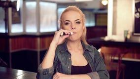 Mulher bonita nova no fumo um cigarro eletrônico na loja do vape video estoque