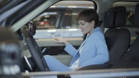 A mulher bonita nova no terno azul do vestuário formal abre a porta do carro e senta-se dentro dela no assento do passageiro dian vídeos de arquivo