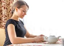 Mulher bonita nova no vestido clássico preto com cabelo escuro longo em um coffe bebendo do caffe na manhã Imagens de Stock