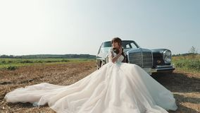 Mulher bonita nova no vestido de casamento que levanta perto do carro do vintage video estoque
