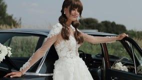 Mulher bonita nova no vestido de casamento que levanta perto do carro do vintage filme