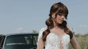 Mulher bonita nova no vestido de casamento que levanta perto do carro do vintage vídeos de arquivo