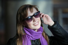 Mulher bonita nova nos óculos de sol com telefone Foto de Stock