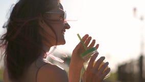 A mulher bonita nova nos óculos de sol está bebendo um cocktail de um frasco de vidro com uma palha em uma rua da cidade vídeos de arquivo