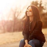 Mulher bonita nova nos óculos de sol no por do sol fotografia de stock