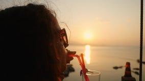 Mulher bonita nova nos óculos de sol que aprecia um cocktail alcoólico do nascer do sol tropical do tequila decorado com a flor n filme