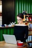 A mulher bonita nova bonita nos vidros usando o portátil no café, fecha-se acima do retrato da mulher de negócio, um computador,  fotografia de stock