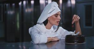 A mulher bonita nova pôs a cereja vermelha sobre o bolo decorado chocolate e sorriu nele alegremente filme