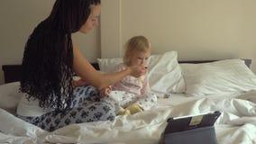 Mulher bonita nova que alimenta o papa de aveia pequeno do bebê ao olhar no tablet pc video estoque