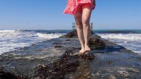 Mulher bonita nova que anda no cais do mar com os pés descalços com as ondas que espirram contra o cais Os p?s fecham-se acima da video estoque