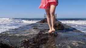 Mulher bonita nova que anda no cais do mar com os p?s descal?os com as ondas que espirram contra o cais Os p?s fecham-se acima da vídeos de arquivo