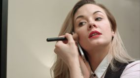 Mulher bonita nova que aplica a composição na cara com escova, tendo o telefonema, estando atrasado Imagem de Stock Royalty Free