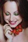 Mulher bonita nova que aprecia morangos e sorriso foto de stock