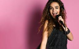 Mulher bonita nova que canta no fim do microfone acima fotografia de stock royalty free