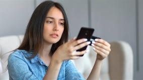 Mulher bonita nova que compra em linha com o cartão de crédito e o smartphone que sentam-se em um sofá na sala de visitas em casa vídeos de arquivo