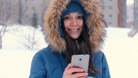 Mulher bonita nova que datilografa uma mensagem em seu telefone celular, a seguir olhando a câmera e o sorriso vídeos de arquivo
