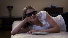 Mulher bonita nova que encontra-se em um sofá Os interruptores na tevê esperta, põem sobre 3d-glasses e olham o filme 3d vídeos de arquivo