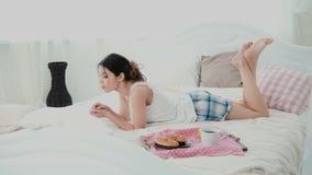 Mulher bonita nova que encontra-se na cama e que usa o portátil A menina moreno surfa o Internet na manhã durante o café da manhã Fotografia de Stock
