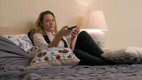 Mulher bonita nova que encontra-se na cama, girando sobre os canais de televisão e usando o smartphone em casa Fotografia de Stock