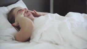 Mulher bonita nova que encontra-se na cama na manhã A menina apenas acordou e olhando o sorriso da câmera Lazer em casa video estoque