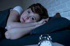 Mulher bonita nova que encontra-se na cama tarde na noite que sofre da insônia que tenta dormir imagem de stock royalty free