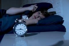 Mulher bonita nova que encontra-se na cama tarde na noite que sofre da insônia que tenta dormir foto de stock royalty free