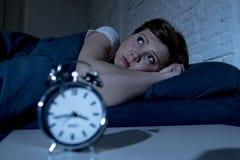 Mulher bonita nova que encontra-se na cama tarde na noite que sofre da insônia que tenta dormir foto de stock