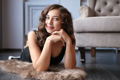 Mulher bonita nova que encontra-se no assoalho lustrado no estúdio Fotografia de Stock