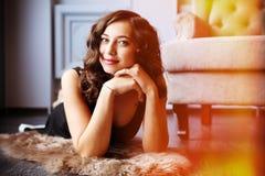 Mulher bonita nova que encontra-se no assoalho lustrado no estúdio Fotos de Stock Royalty Free
