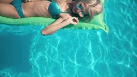 Mulher bonita nova que encontra-se no colchão de ar na piscina Fotografia de Stock