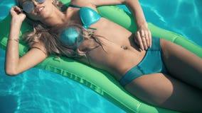 Mulher bonita nova que encontra-se no colchão de ar na piscina Fotografia de Stock Royalty Free