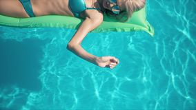 Mulher bonita nova que encontra-se no colchão de ar na piscina Foto de Stock