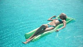 Mulher bonita nova que encontra-se no colchão de ar na piscina Foto de Stock Royalty Free