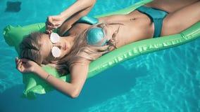 Mulher bonita nova que encontra-se no colchão de ar na piscina Imagem de Stock Royalty Free
